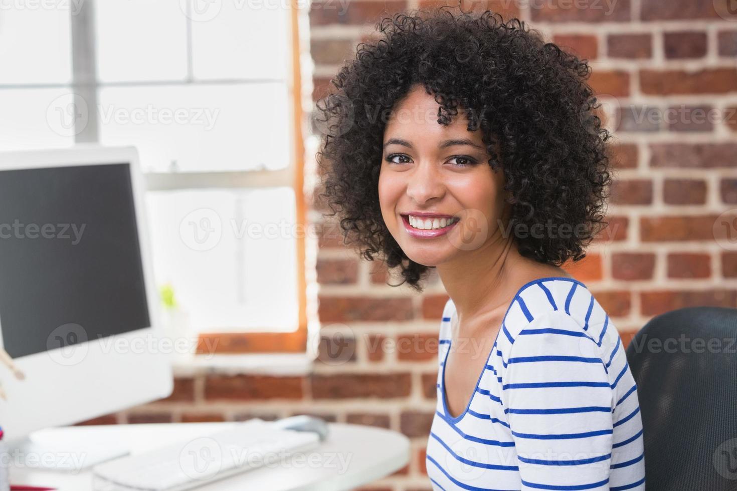 éditeur de photos de femme souriante à l'aide d'ordinateur dans le bureau