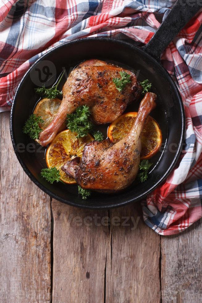 Cuisse de canard frit avec des oranges dans la vue verticale de dessus de casserole photo