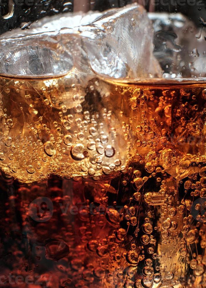 bulles dans le verre de cola avec de la glace. photo