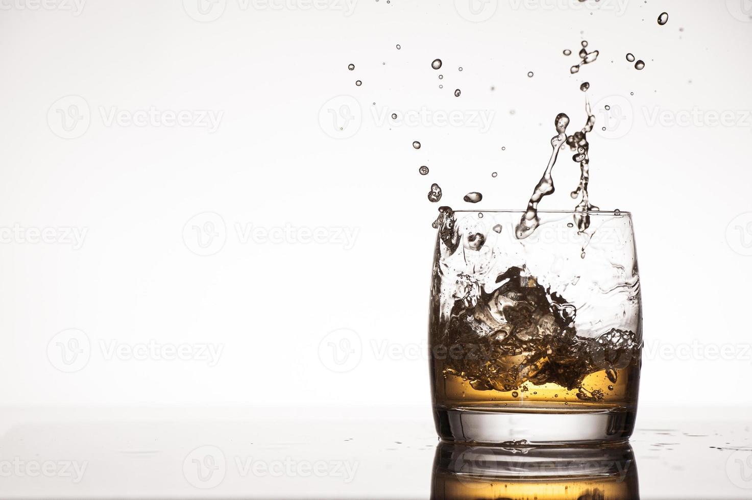 éclaboussures de glace dans le whisky ou le brandy photo