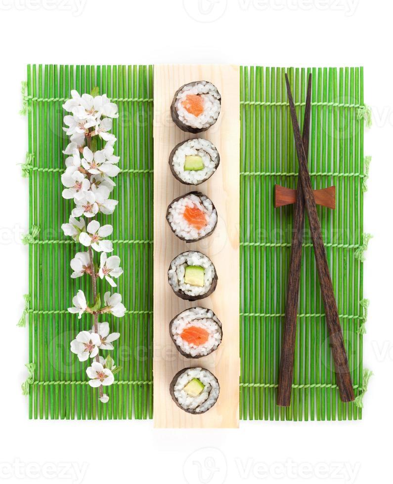 sushi maki avec saumon et concombre et branche de sakura photo