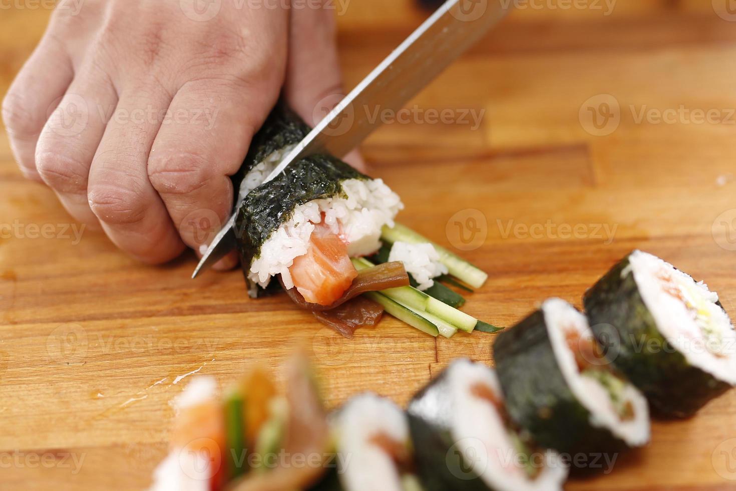 couteau à sushi maître trancher des rouleaux de sushi photo