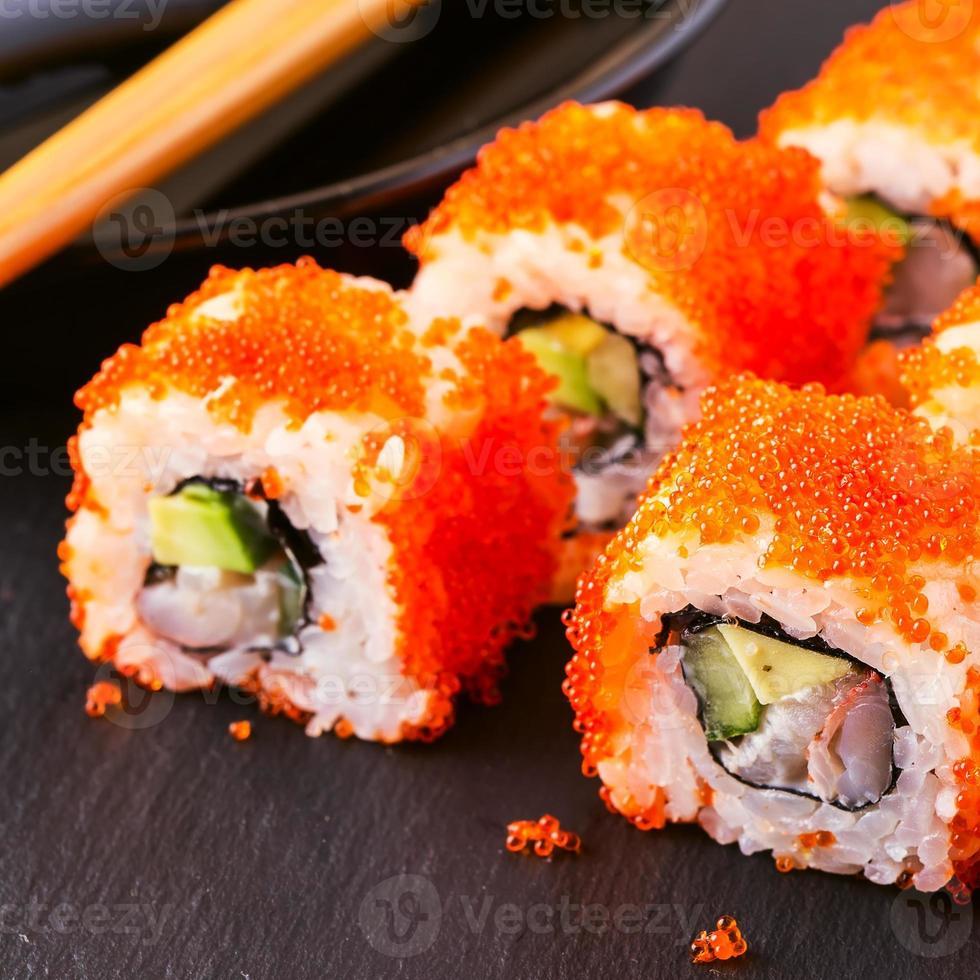 rouleau de sushi au crabe, avocat, concombre et tobiko. photo