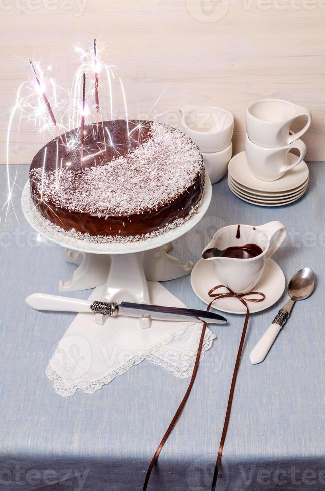 Gâteau de fête avec glaçage au chocolat sur table servi en vaisselle blanche photo