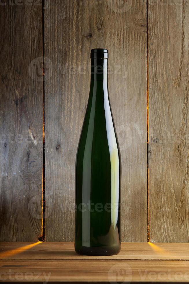 simple bouteille de vin devant un mur en bois photo