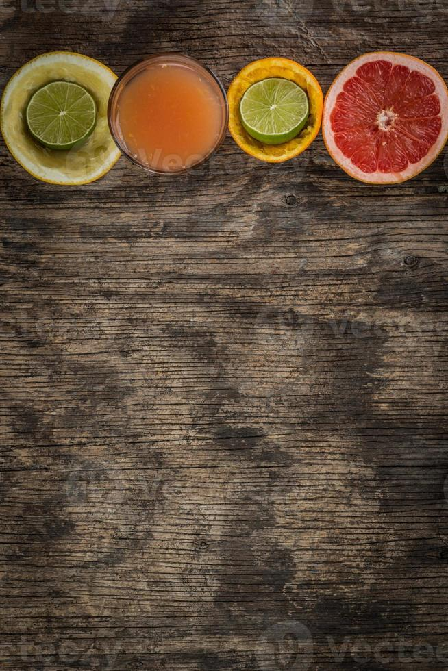 verre de jus et agrumes frais sur bois rustique photo