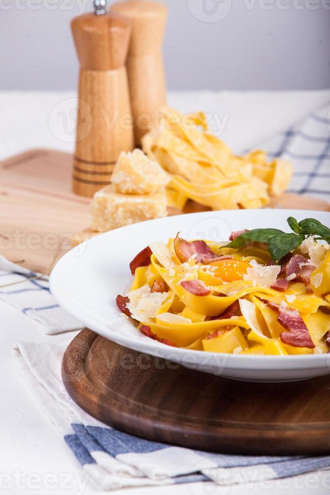 pâtes carbonara aux spaghettis tagliatelles, jaune d'oeuf, bacon et basilic. photo
