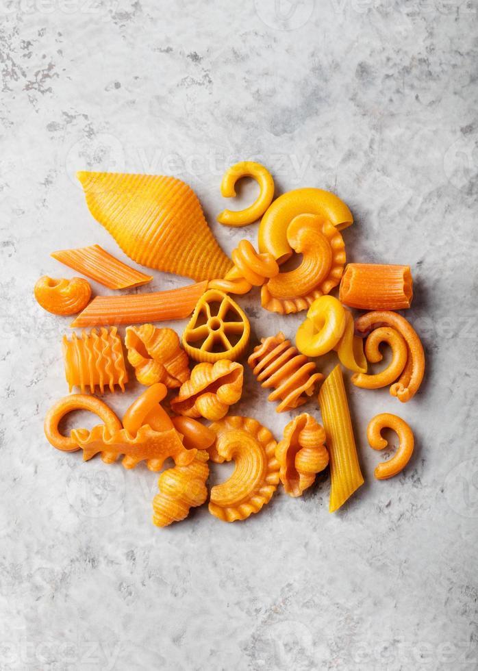 tas de pâtes orange de couleur naturelle avec carotte photo