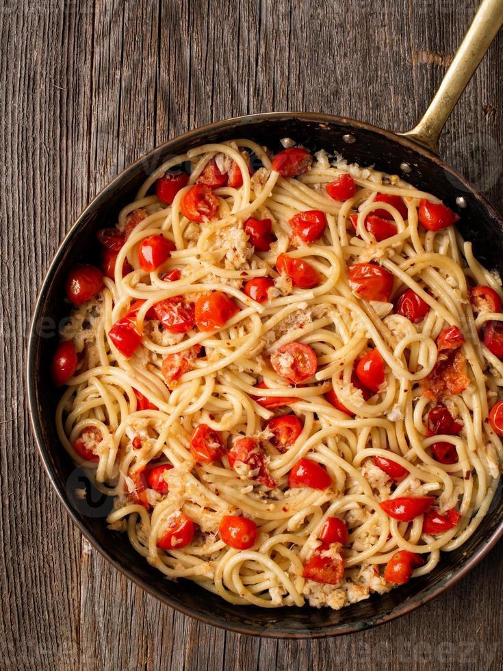 pâtes spaghetti au crabe italien épicé rustique et aux tomates cerises photo
