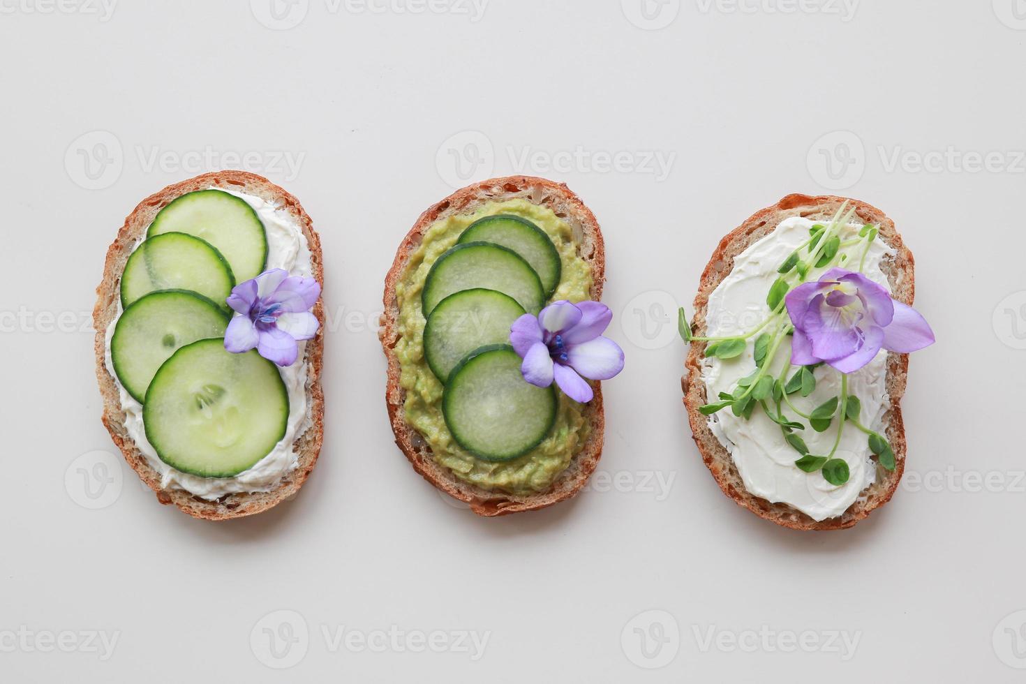 Sandwichs au visage vert au levain avec fleurs comestibles violettes photo