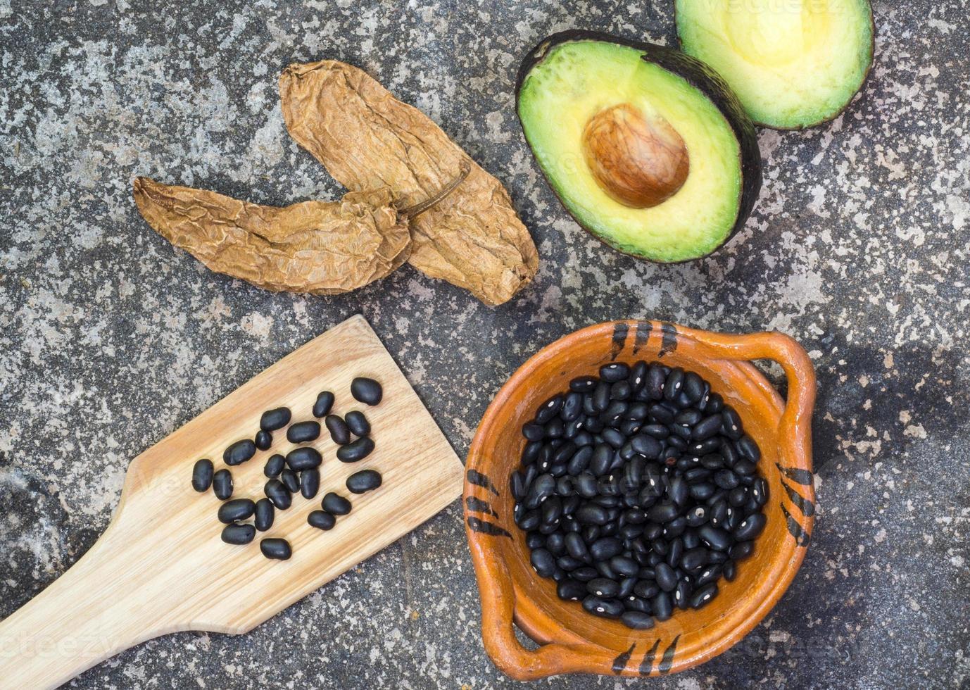 avocat, piments chili et haricots noirs sur moulin à pierre photo