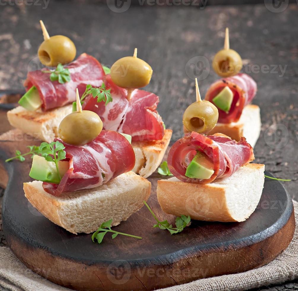 grignoter des toasts avec jambon, avocat et olives photo