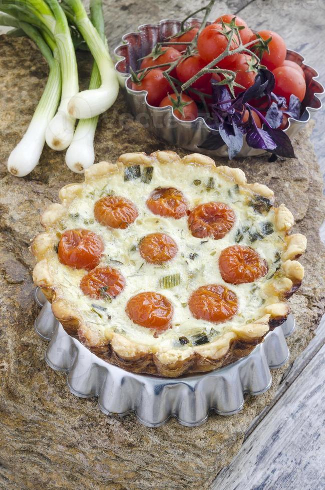 Tarte aux tomates cerises et oignons sur un plat allant au four en aluminium photo