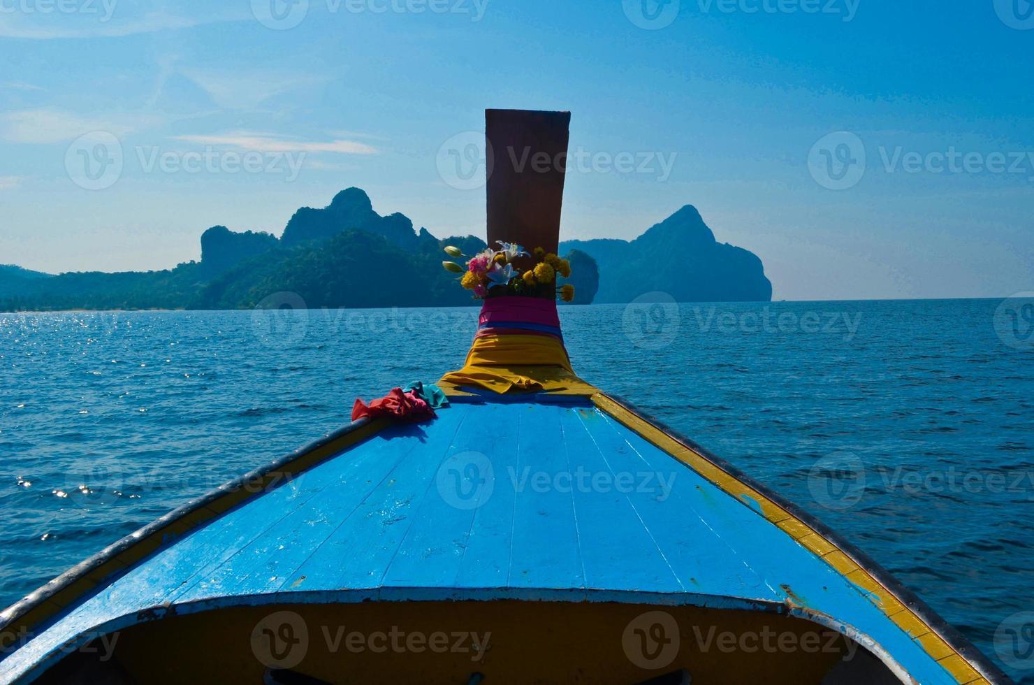 bateau longtail naviguant dans l'île de phiphi, thaïlande photo
