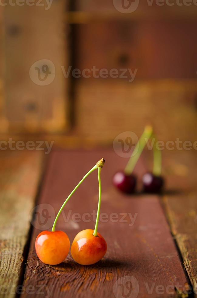 cerises rouges et jaunes sur fond de bois photo