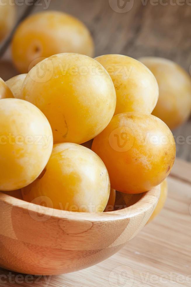 prunes jaunes juteuses mûres dans un bol en bois photo