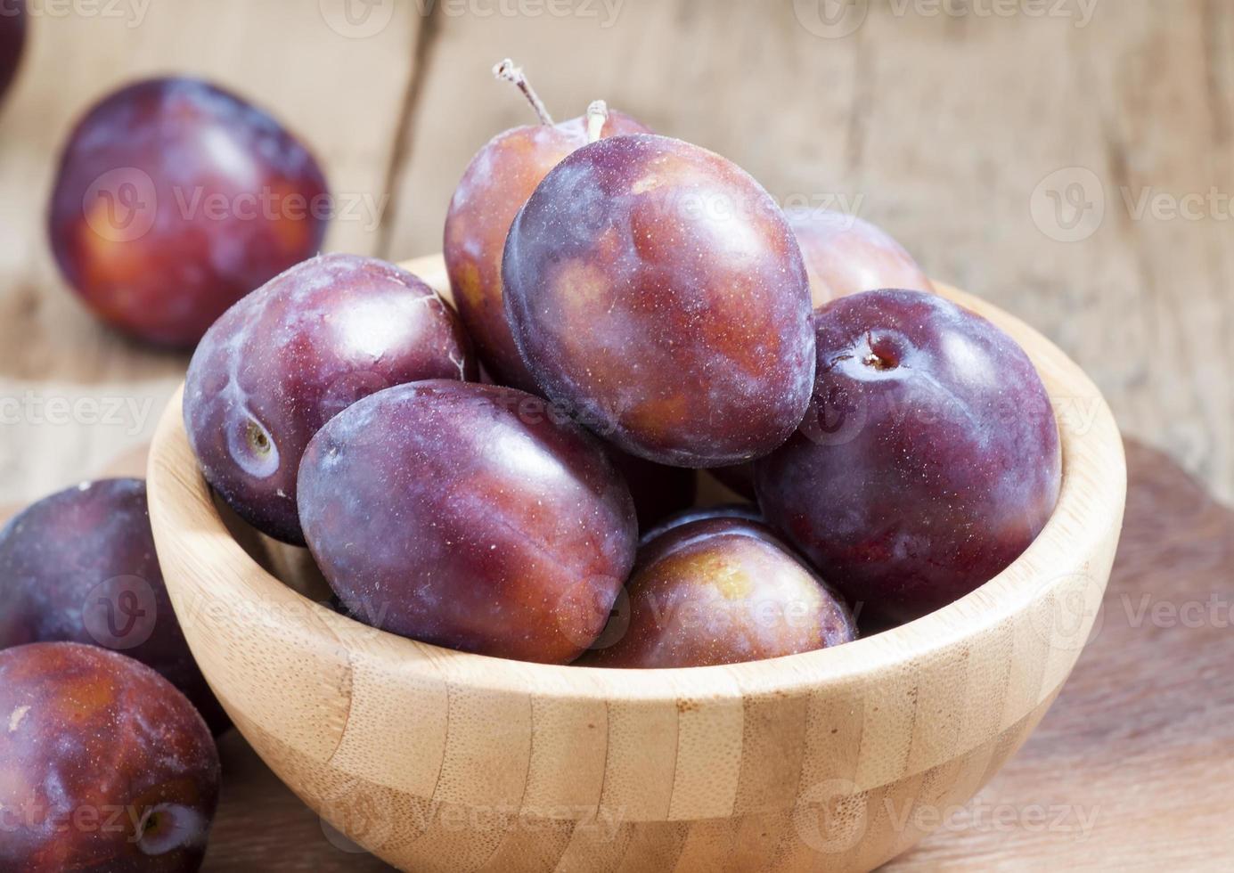 délicieuses prunes bleues dans un bol en bois photo