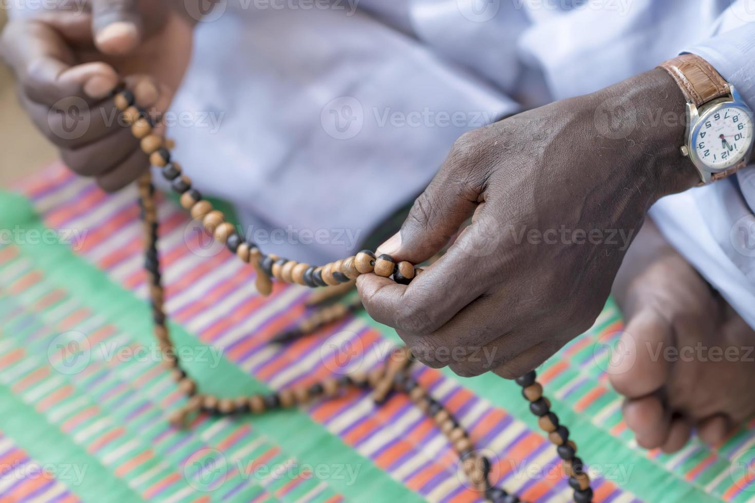 mains d'un homme musulman priant avec un chapelet photo