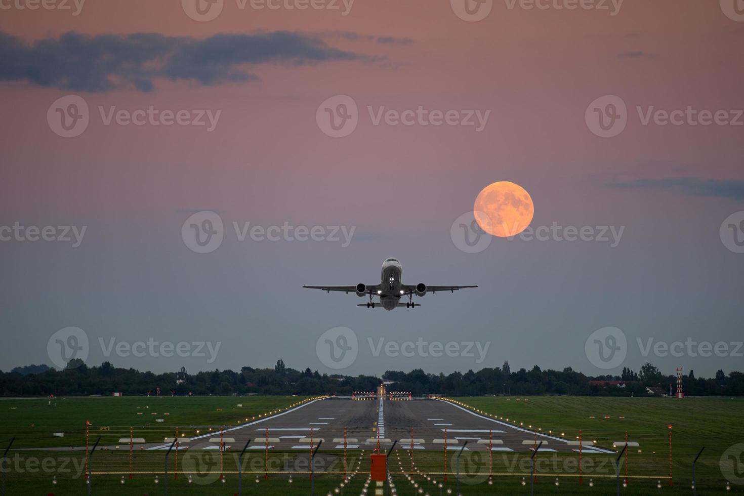 décollage d'avion sous la pleine lune photo