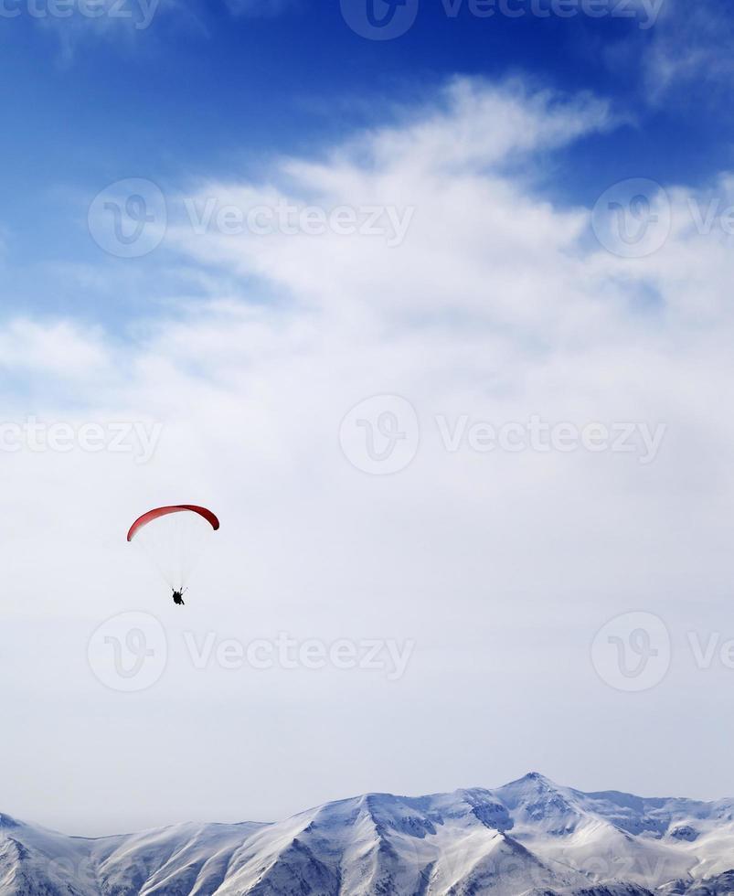 silhouette parachutiste des montagnes dans le ciel venteux photo