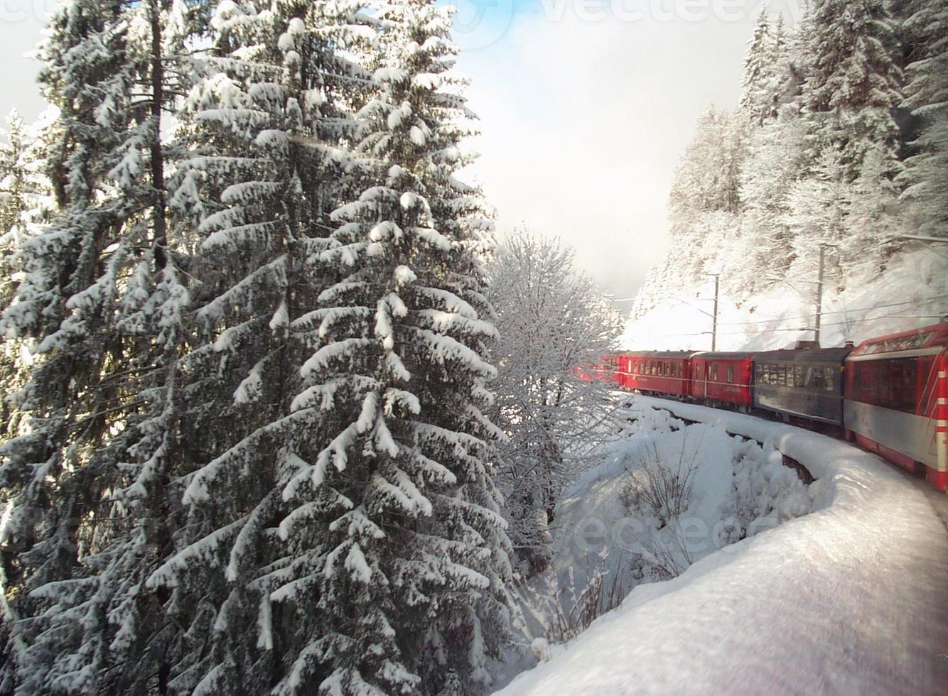 Train suisse voyageant à travers les Alpes en hiver photo