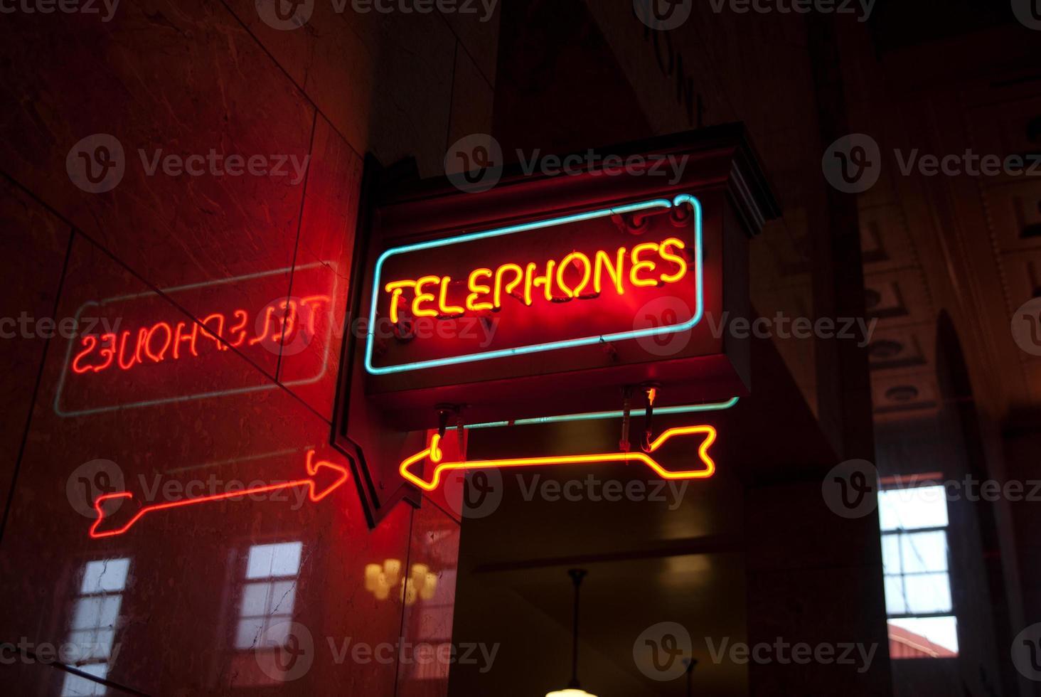 enseigne au néon pointant vers les téléphones publics photo