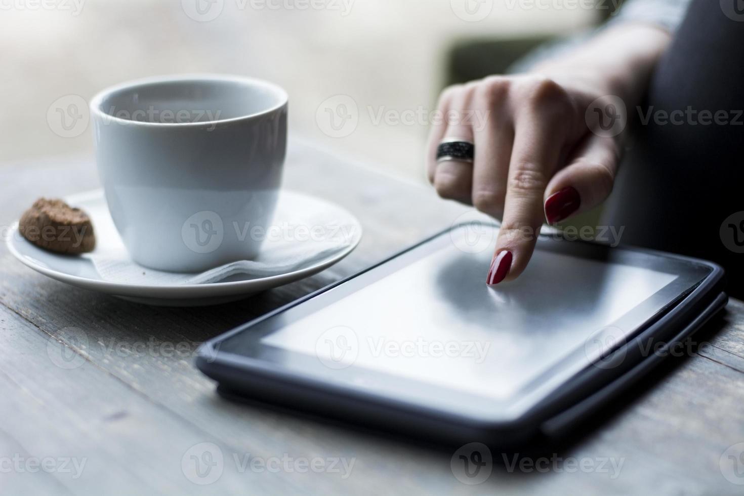 main féminine parcourant sur tablette photo