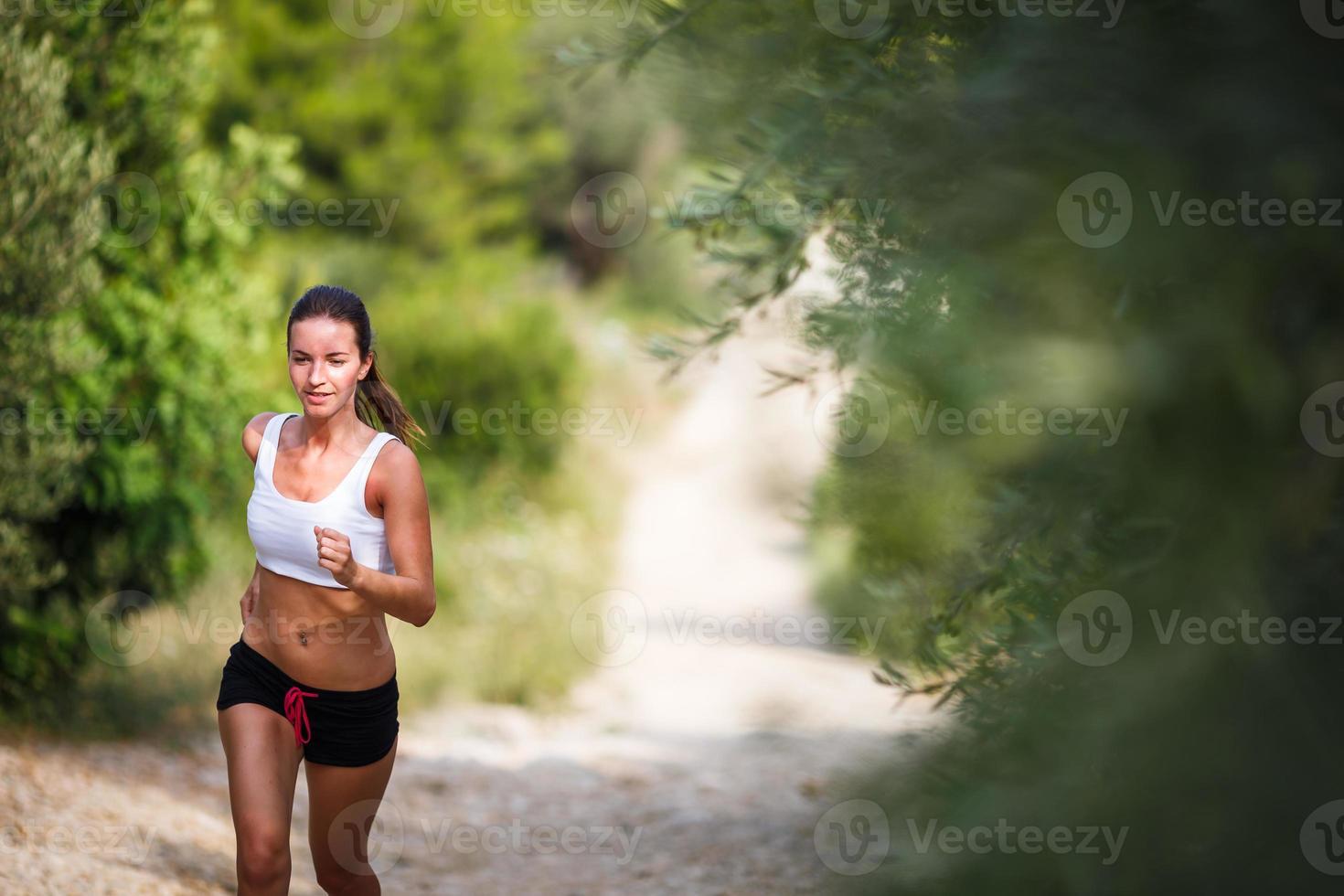 belle jeune coureuse sur un chemin forestier photo