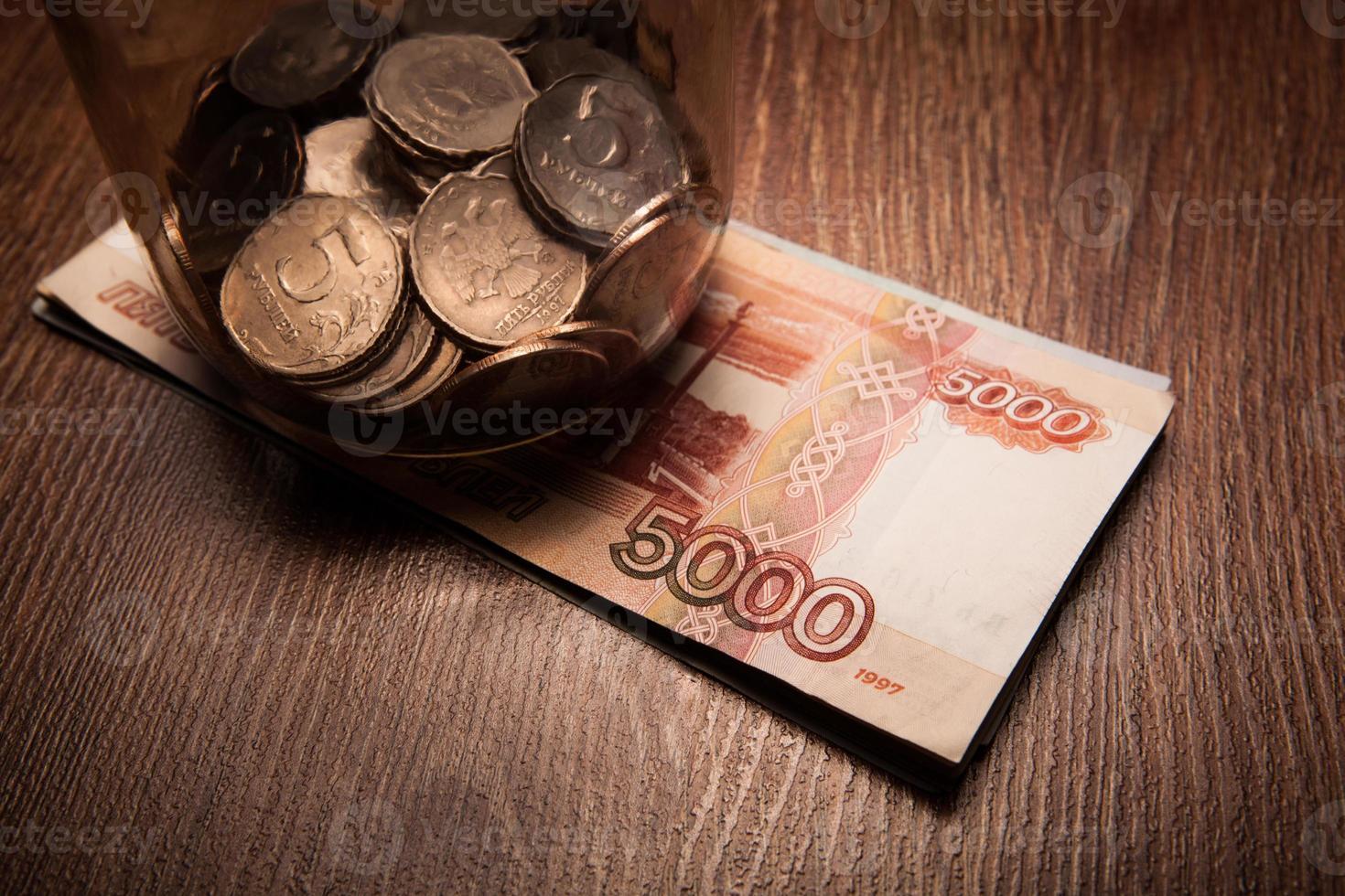 paquet de billets de banque et un bocal en verre avec des pièces photo