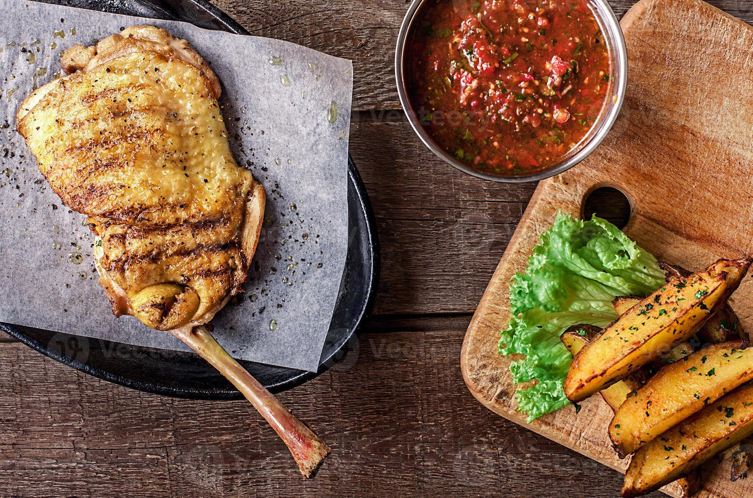 viande de poulet frite sur l'os, quartiers de pommes de terre, laitue photo