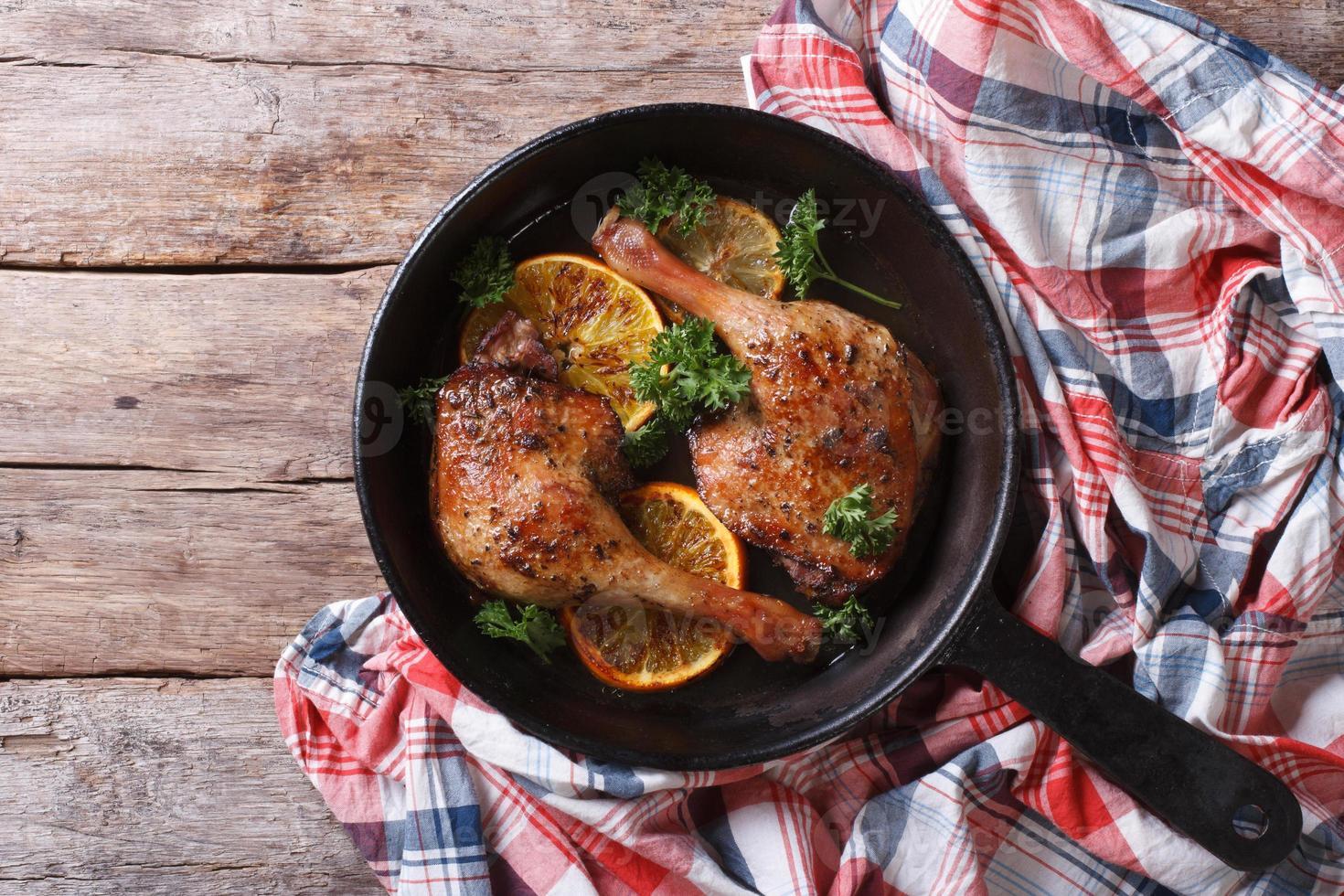 délicieux cuisse de canard rôti avec gros plan d'oranges. vue de dessus photo