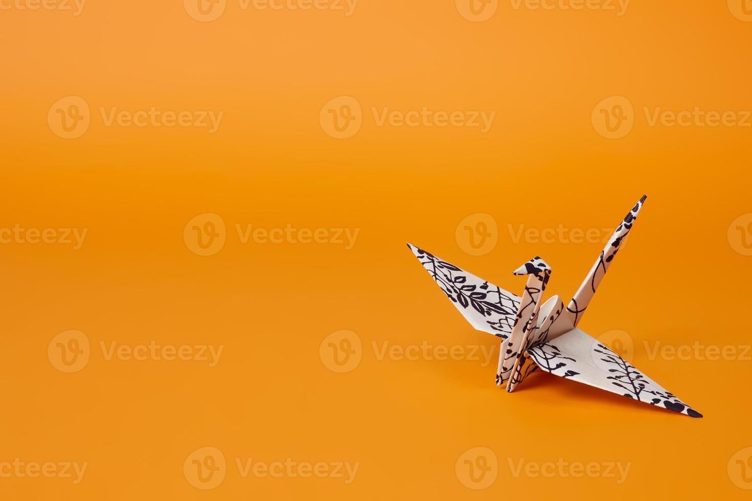 grue origami sur fond orange photo
