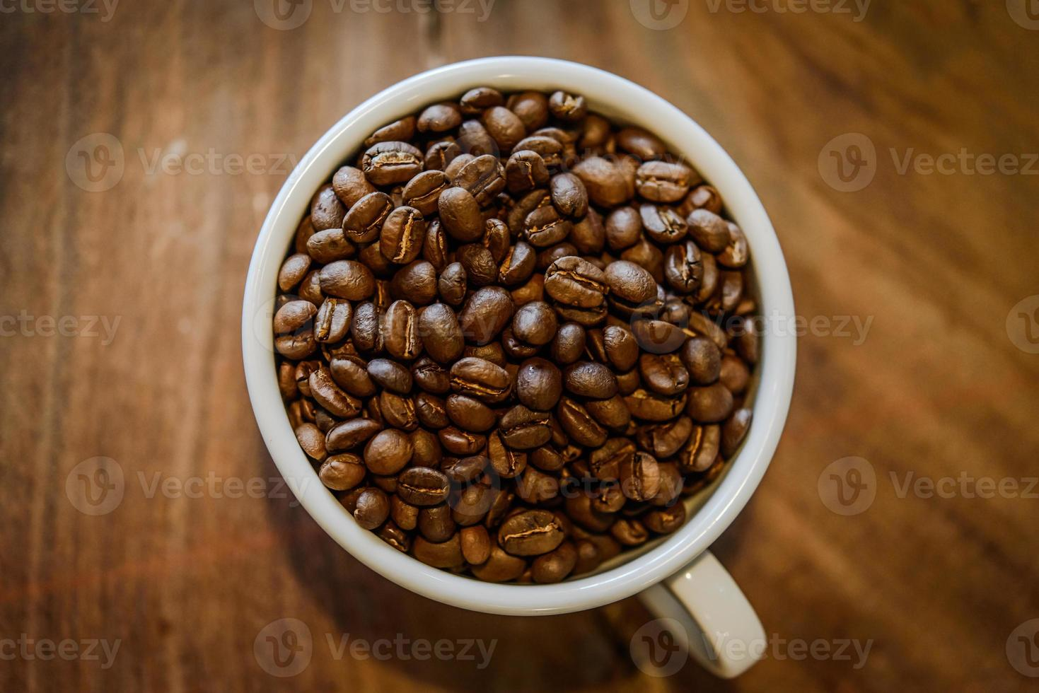 grains de café en tasse sur fond de bois grunge photo