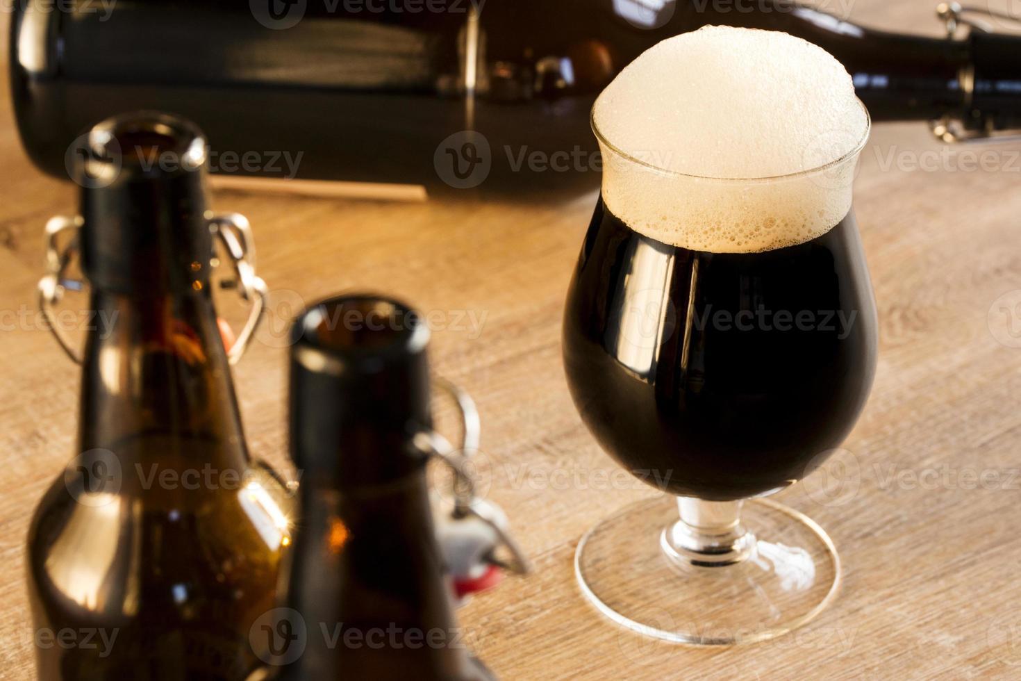 bière brune en verre, sur la table photo