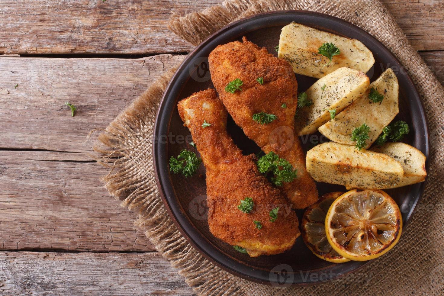 cuisses de poulet dans la pâte, avec pommes de terre sur plaque gros plan. Haut photo