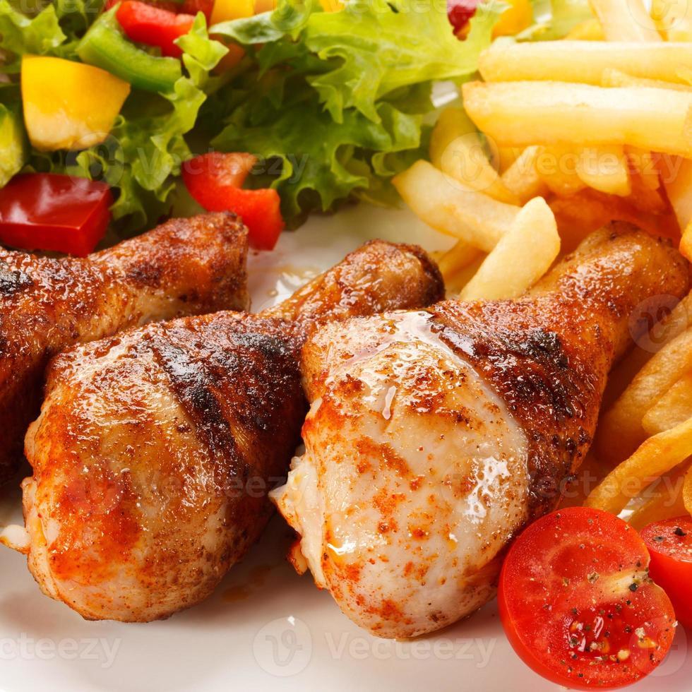 pilons de poulet rôti, frites et légumes photo