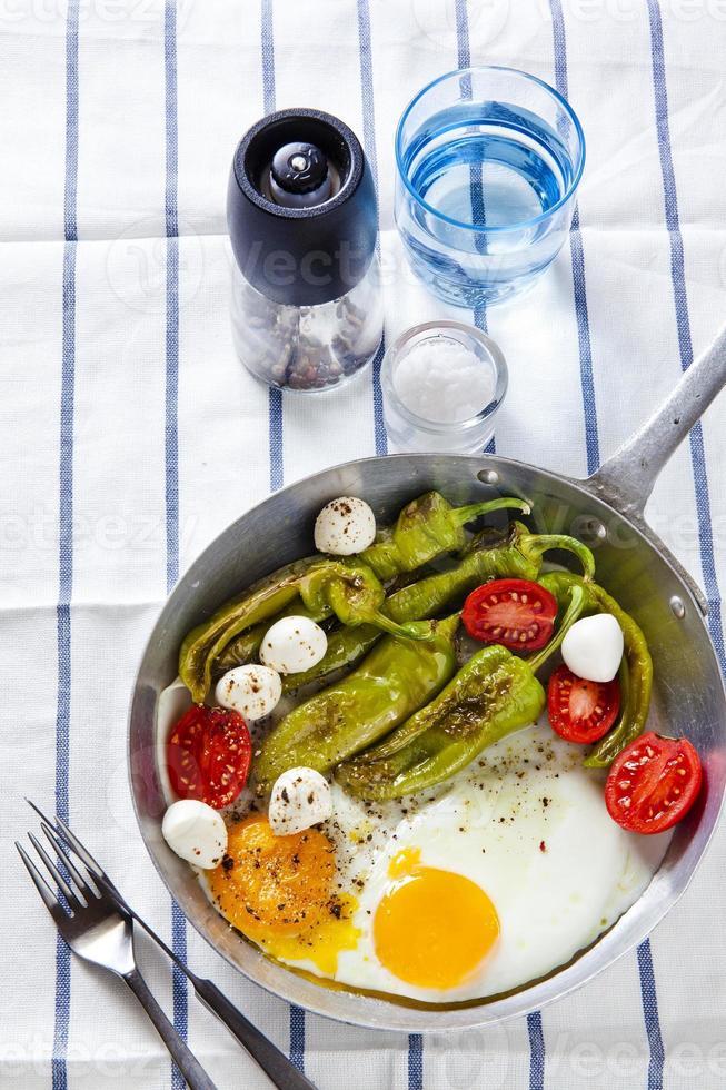 petit déjeuner dans une poêle. oeufs au plat avec salade. photo
