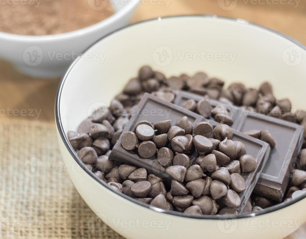 pépites de chocolat et barre de chocolat noir dans un bol blanc. photo