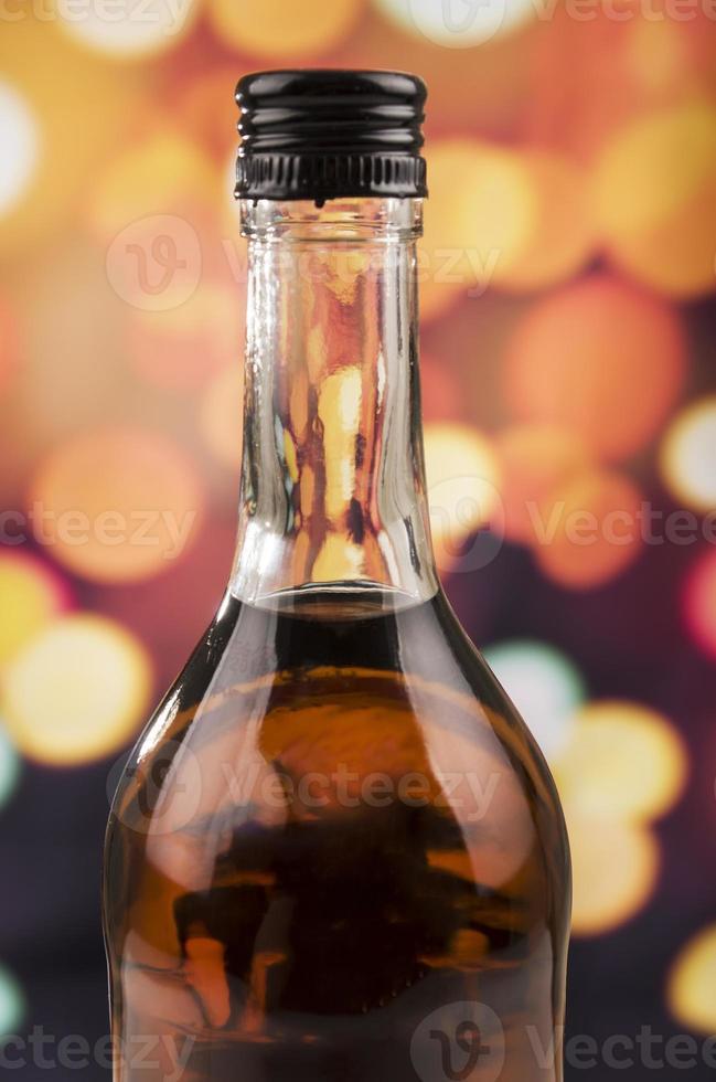 bouteille de rhum whisky sur fond de lumières défocalisées photo