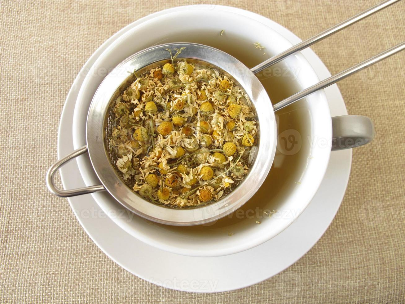 thé de fleurs de camomille dans une passoire à thé photo
