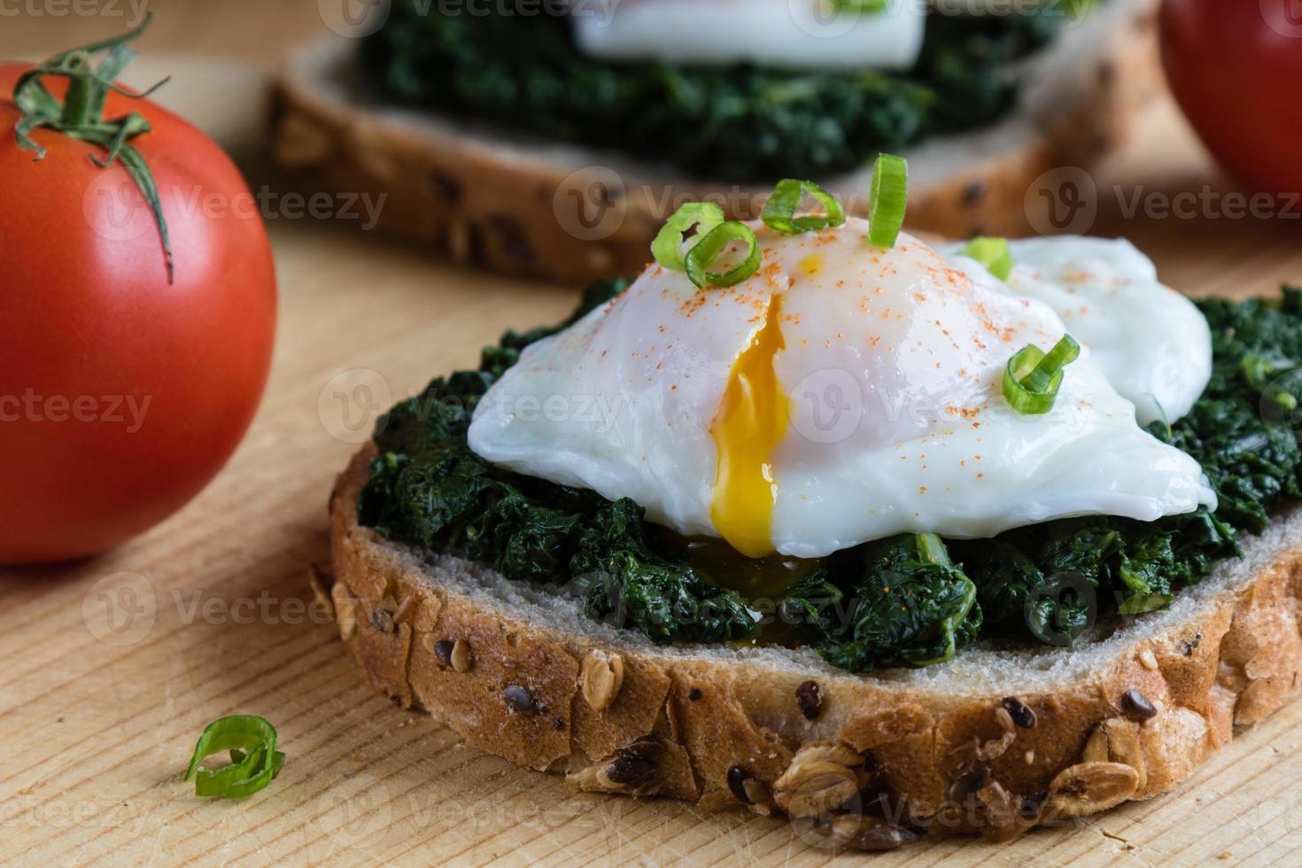 épinards et œuf poché sur pain brun photo