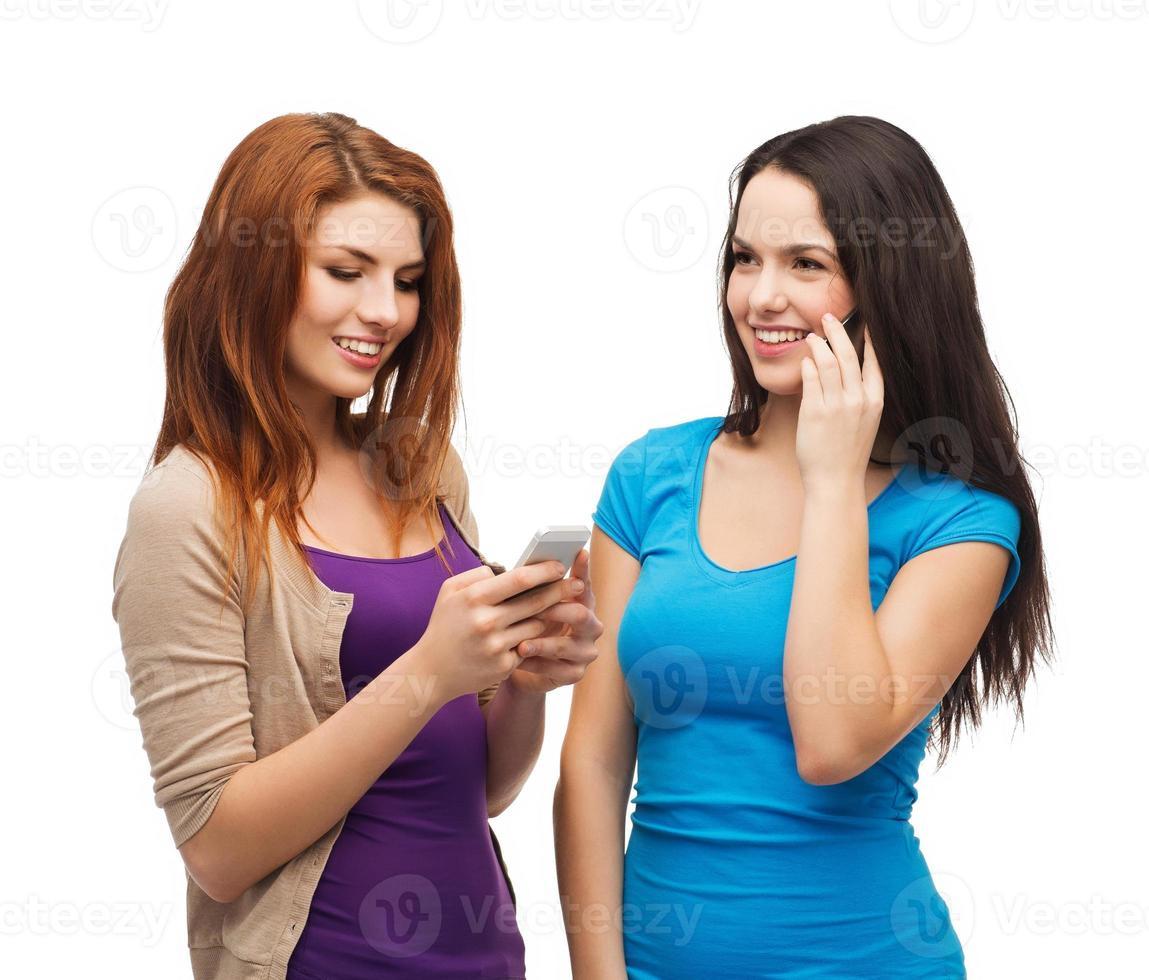 deux adolescentes souriantes avec les smartphones photo