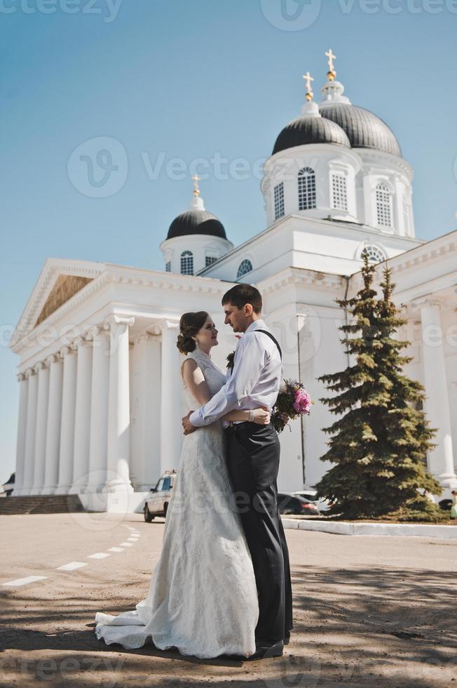 le couple se tient devant les colonnes blanches photo
