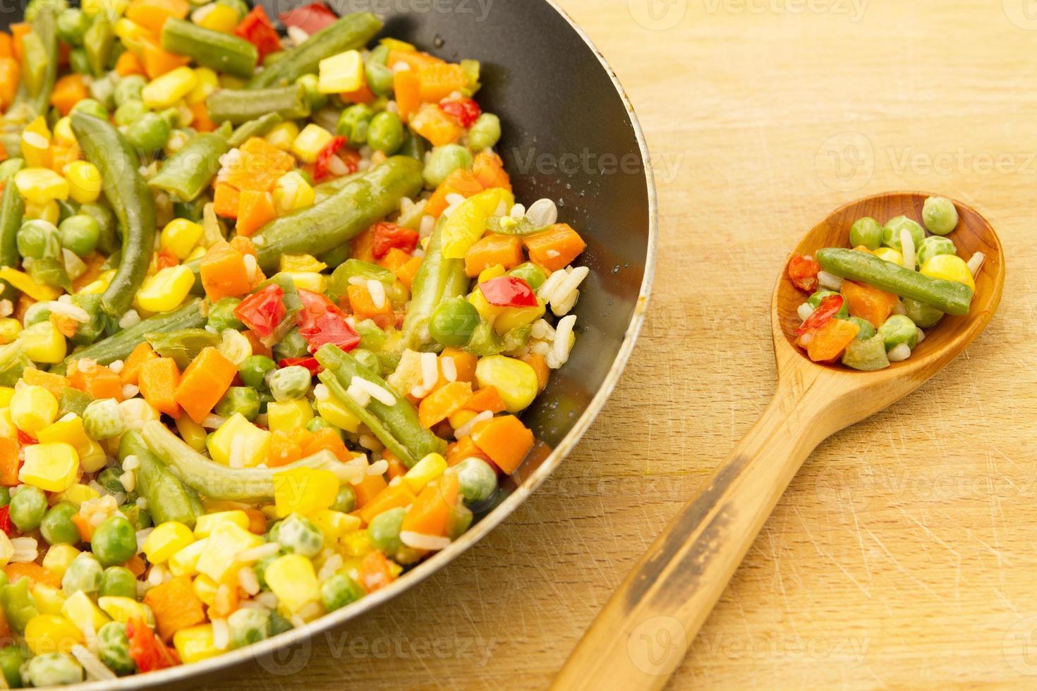 mélange de légumes dans la poêle sur fond de bois photo