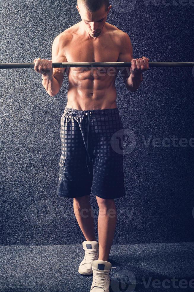 bodybuilder, soulever des poids dans la salle de gym photo