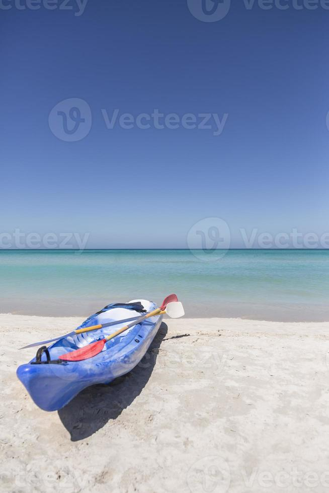 Kayak bleu reposant sur le sable blanc des Caraïbes photo