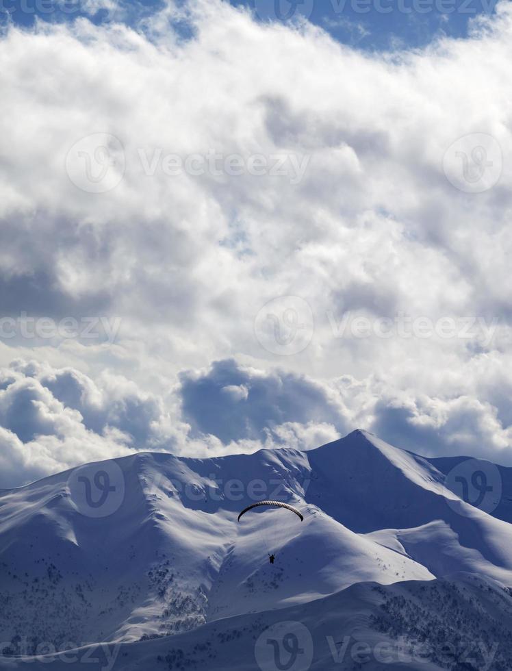 Montagne du soleil du soir et silhouette de parapente photo