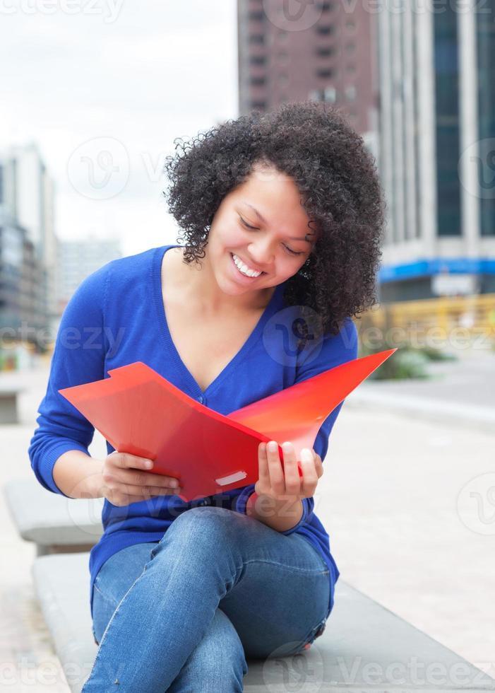 Étudiant latin en riant aux cheveux bouclés, lecture de document en ville photo