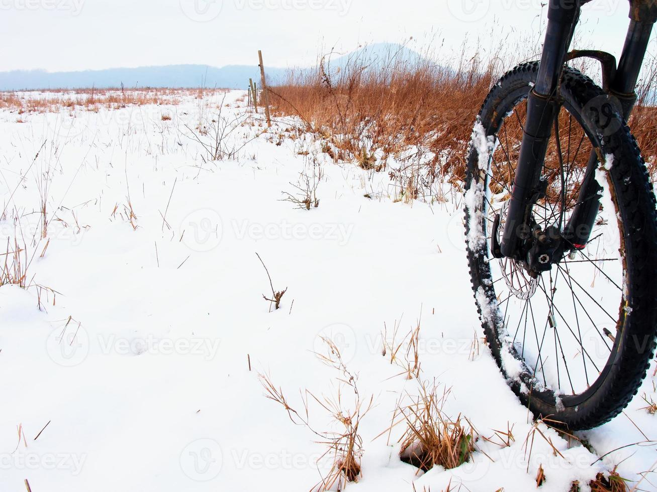 la roue avant du VTT dans la première neige. photo
