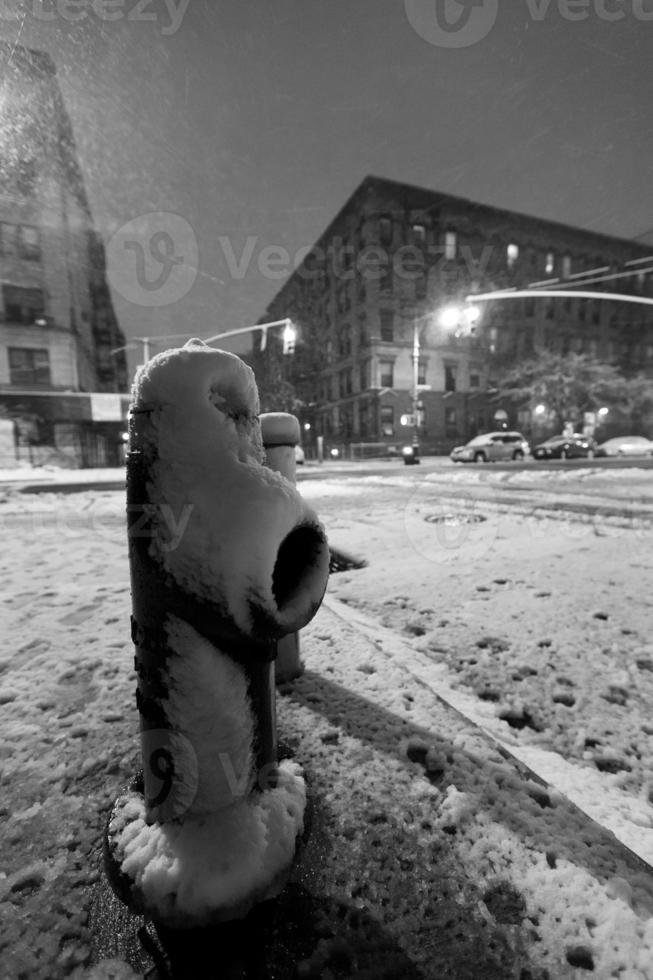 Bouche d'incendie couverte de neige et Harlem Manhattan Street de nuit photo